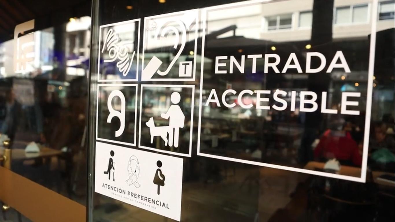 """Puerta de ingreso a Bar Facal. En el vidrio se lee """"entrada accesible"""" y se ven signos que indican que es un lugar accesible para diferentes tipos de discapacidad"""
