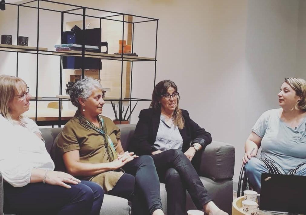 Cuatro mujeres sentadas charlan en estudio de TV