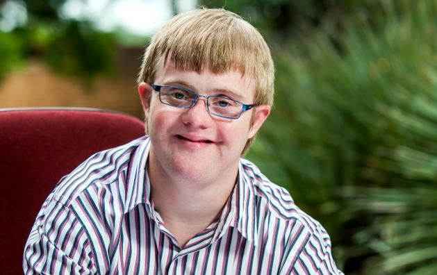Chico con síndrome de Down mira a la cámara y sonríe