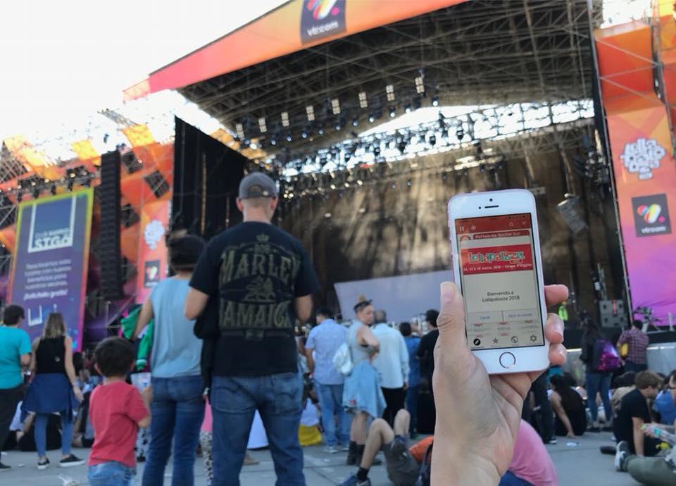 Foto muestra celular de en primer plano con App Lazarillo de fondo. La persona que lo sostiene está en una fiesta al aire libre.