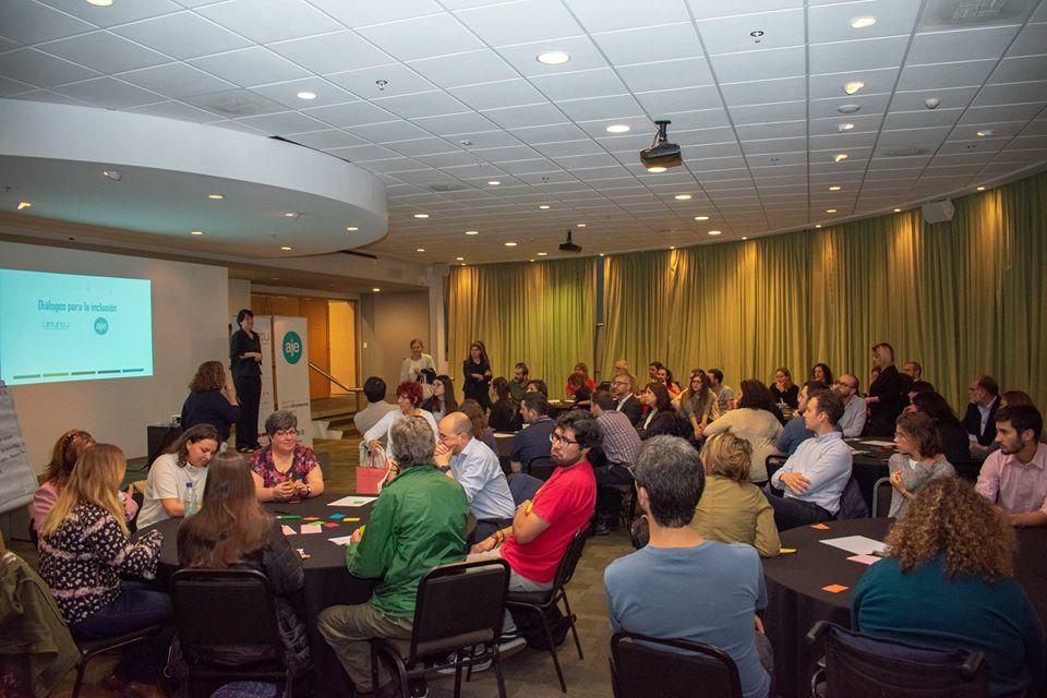 Salón lleno de gente sentada en mesas redondas