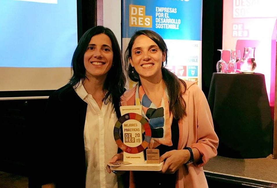 Dos mujeres sostienen un premio y miran a la cámara
