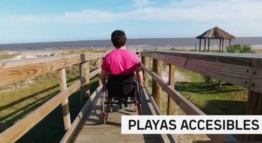 Foto que muestra a un joven en silla de ruedas bajando a la playa