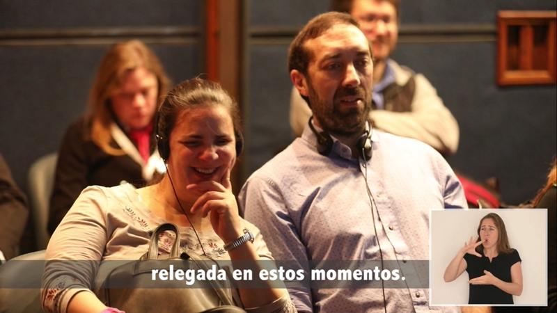 Dos personas ciegas en conferencia escuchan audiodescripción