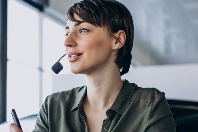 Una joven morocha y sonriente hablando a traves de un auricular